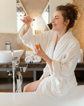 Donna in accappatoio preparazione vasca da bagno