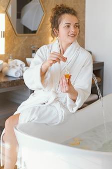 Woman in bath robe preparing bathtub