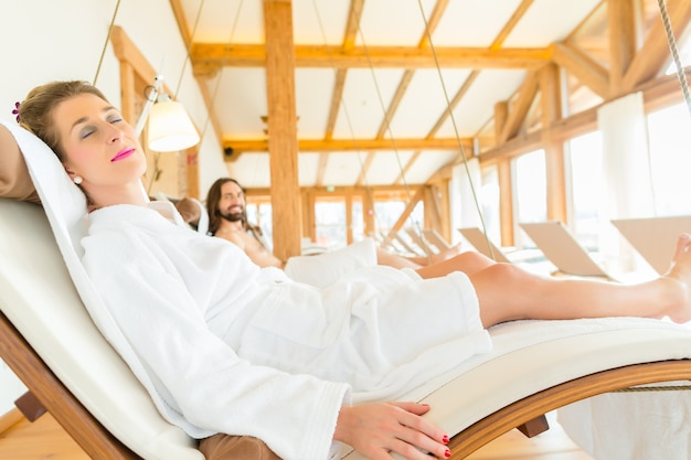 Woman in bath robe relaxing or sleeping on swing lounger in wellness spa relaxation room