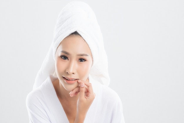 Woman in bath towel is touching her face and smiling isolated on white.