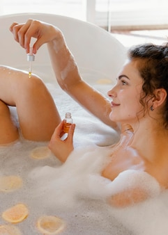 Woman bathing with orange slices in bath