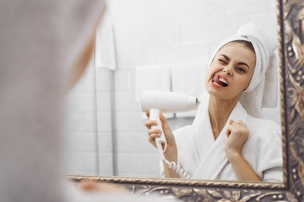 A woman in a bathrobe in a bathrobe in front of a mirror looks at her face