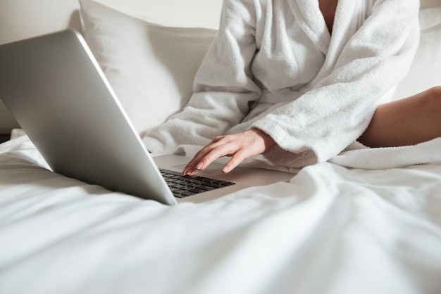 Woman in bathrobe on bed and using laptop