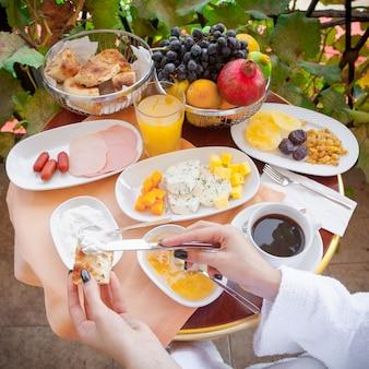 Donna in un accappatoio che mangia prima colazione fuori nella vista laterale di mattina