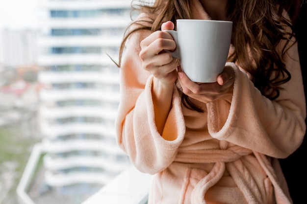 Woman in bathrobe holding cup of hot tea. outumn mood.