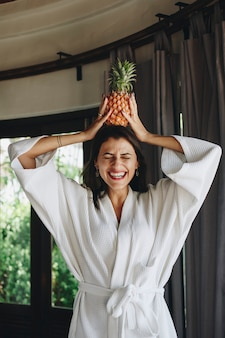 Woman in a bathrobe holding a pineapple
