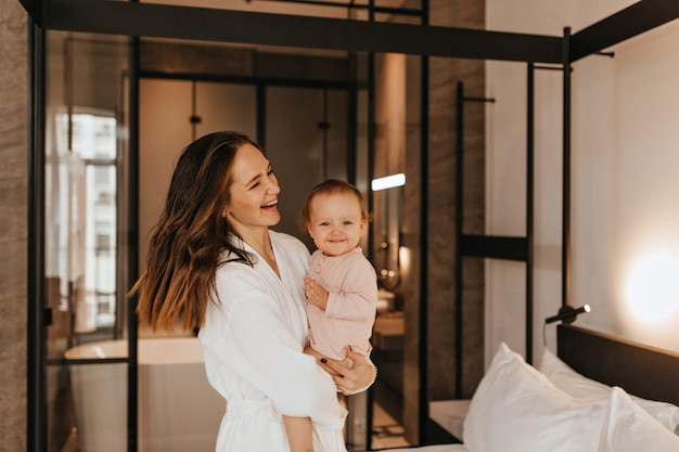 Woman in bathrobe holds small, smiling child. portrait of mother with daughter in bedroom.
