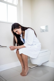 Woman in bathrobe looking at her pregnant test in toilet