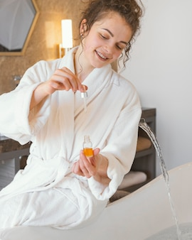 Woman in bathrobe pouring serum in bathtub