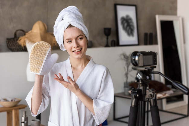 Woman in bathrobe presenting bath accessories