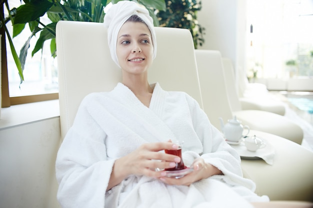 Woman in bathrobe relaxing by pool in spa