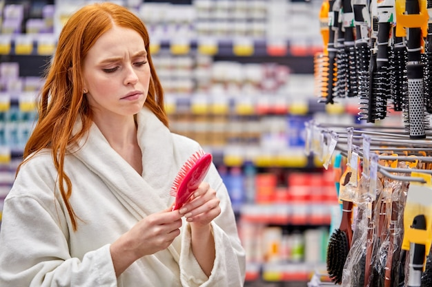 Woman in bathrobe seriously looking at comb in store, studying before purchase. in bathrobe, shopping concept