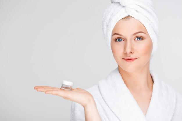 Donna in accappatoio mostrando crema, essenza lifting