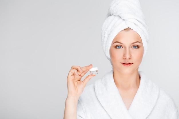 Woman in bathrobe showing cream, eye lifting essence