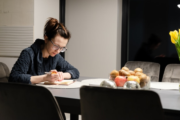 Woman in a bathrobe sits at a table at night and writes in a notebook