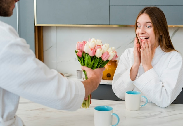 Woman in bathrobe surprised with bouquet of tulips
