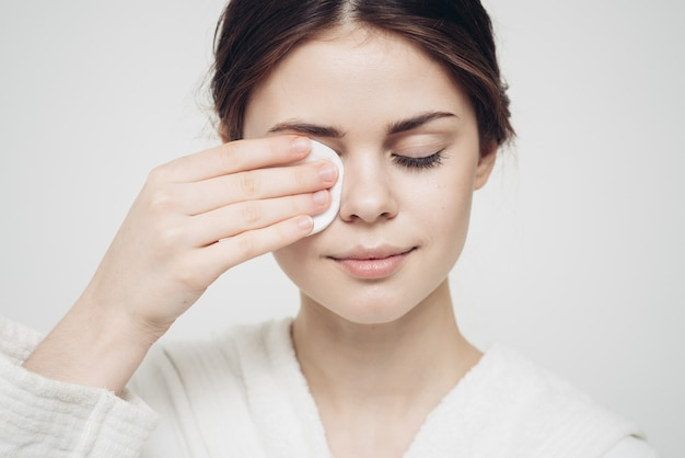 Woman in a bathrobe wipes her face with a white sponge appearance care cosmetology. high quality photo