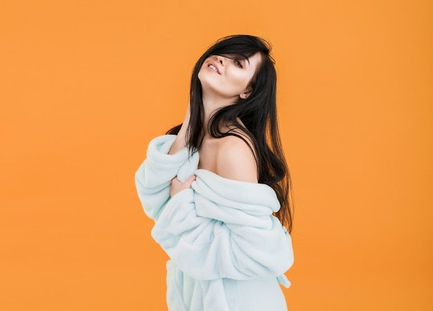 Woman in bathrobe with bare shoulders posing on orange background
