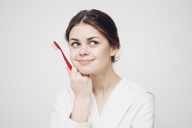 Woman in a bathrobe with a toothbrush