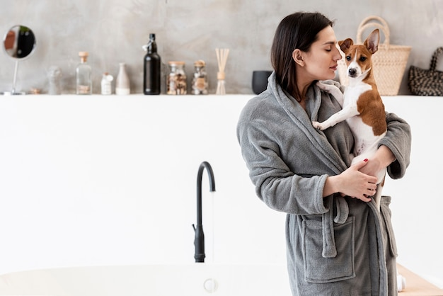 Woman in bathroom holding her dog