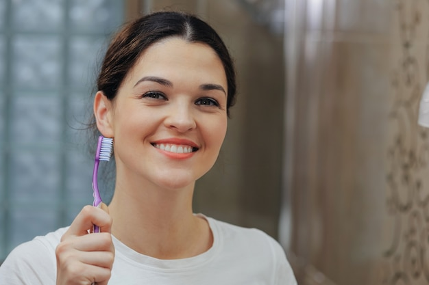 Woman in the bathroom holds a toothbrush in her hands and smiles