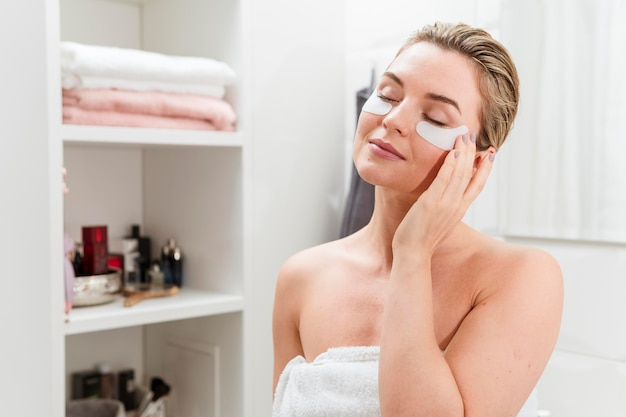 Woman in bathroom with under eye bags treatment
