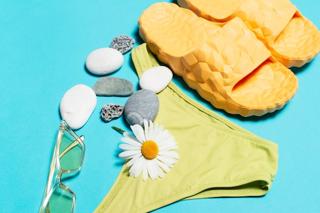 Woman beach accessories, swimsuit, slippers and sunglasses  background
