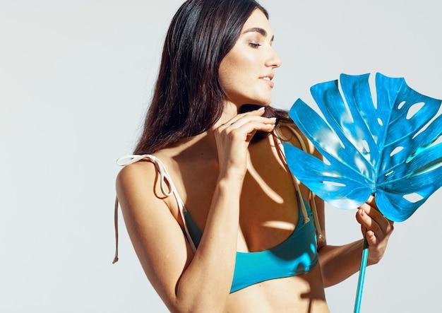 Woman in beach bikini palm leaf glamor posing