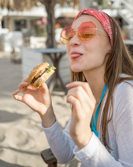 Woman on the beach eating a burger