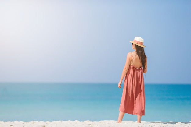 Woman on the beach enjoying summer holidays looking at the sea