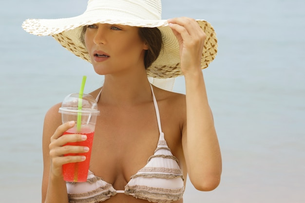 Woman in beach hat with a cocktail