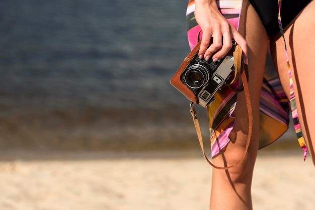 Donna in spiaggia tenendo la fotocamera con copia spazio