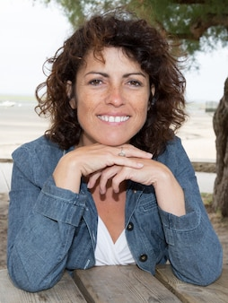 Woman at the beach sitting and smiling