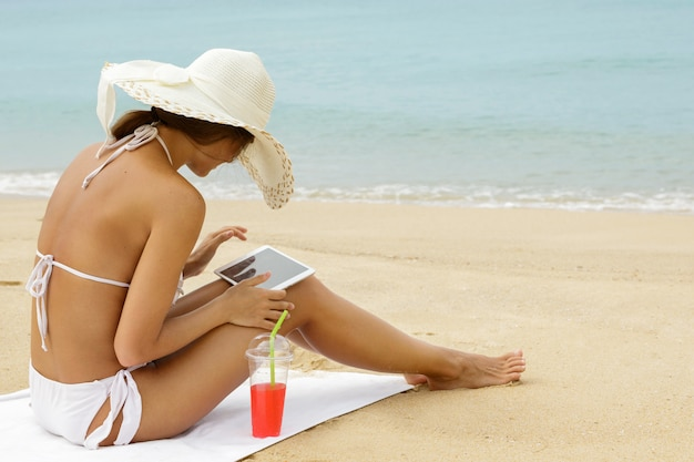 Woman on the beach with a glass of cocktail and tablet pc