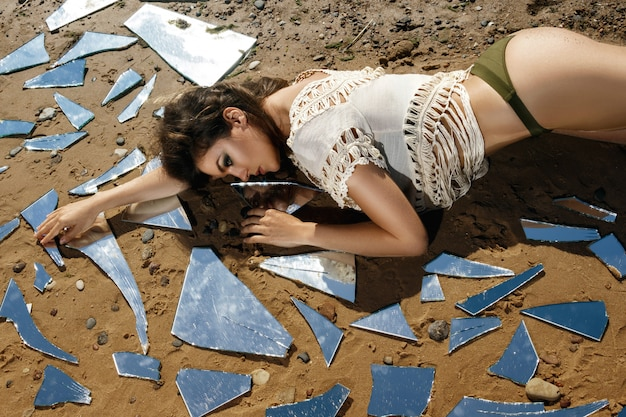 Woman on the beach with a shards of mirror