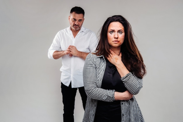 A woman beaten by her husband standing behind her and looking at her aggressively. domestic violence.