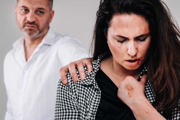 A woman beaten by her husband standing behind her and looking at her aggressively.
