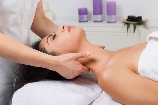 Woman beautician doctor make neck massage in spa wellness center