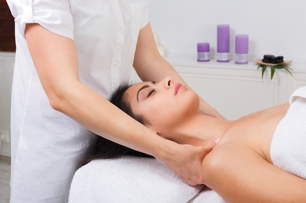 Woman beautician makes neck massage in spa wellness center