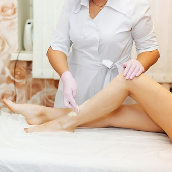 Woman beautician in the procedure of removing hair on the legs of a girl with sugar depilation
