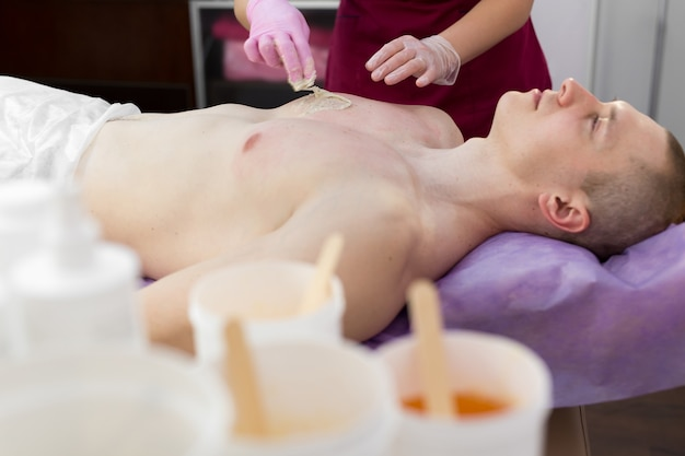 Woman beautician puts a thick sugar paste on the mans chest making him hair removal
