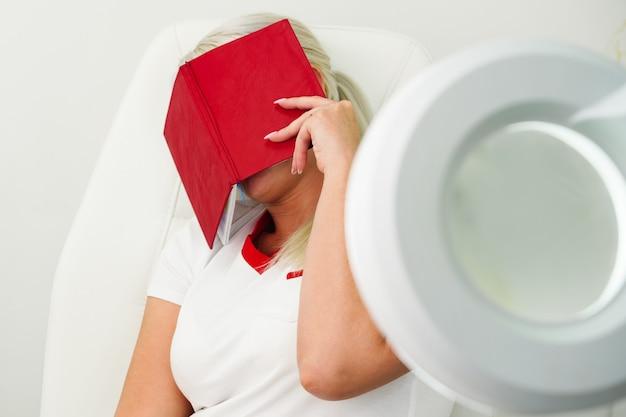 女性の美容師は、疲れた白い肘掛け椅子に座って、7日間赤いノートで顔を覆った...