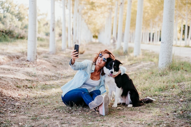 Woman and beautiful border collie dog sitting in a path of trees outdoors. woman taking a selfie with mobile phone