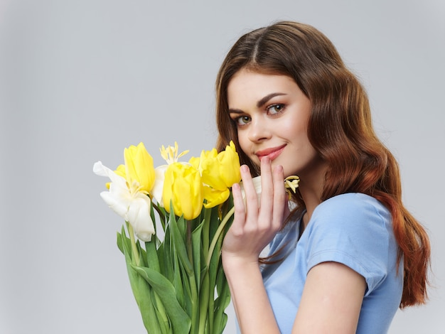 Woman in a beautiful dress with flowers on march 8, gifts flowers light background valentine's day