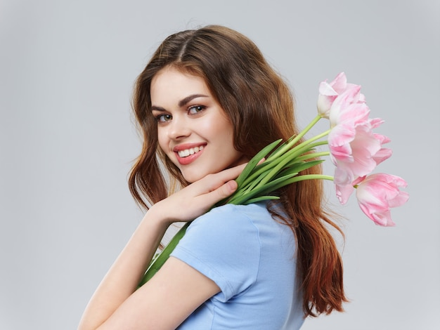 Woman in a beautiful dress with flowers on march 8, gifts flowers light surface valentine's day studio