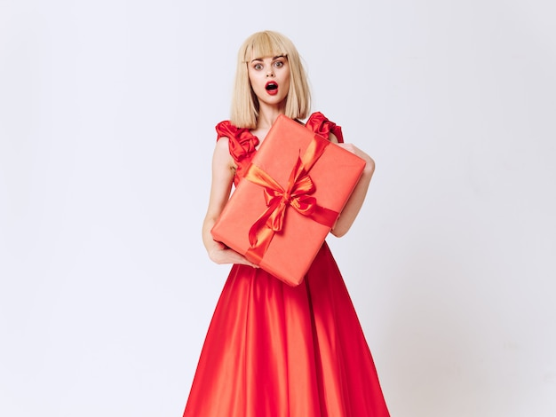 Woman in a beautiful dress with gift holiday boxes in the studio, sale and celebration