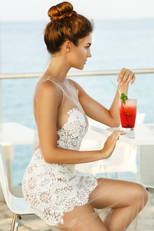 Woman in beautiful dress with glass of cocktail