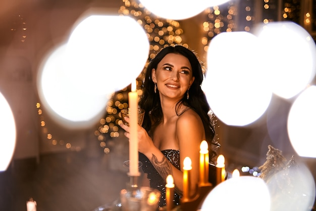 Woman in beautiful dress with glass of sparkling wine over christmas lights