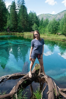 Woman at beautiful geyser lake with thermal springs that periodically throw blue clay and silt from ...