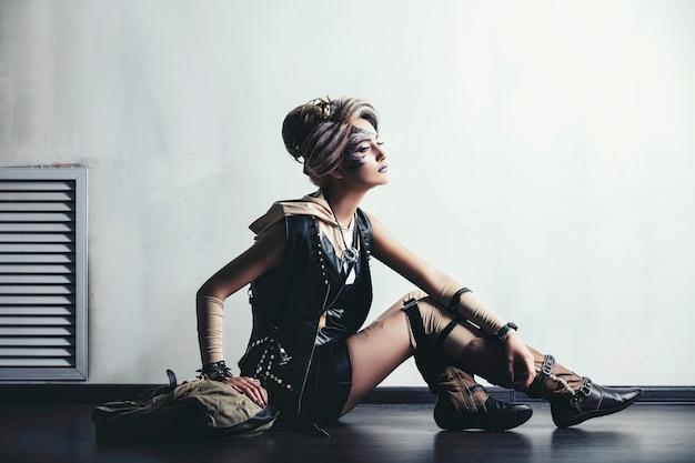 Женщина красивая модель с боди-артом на лице необычной и модной одежды